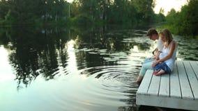 Família que senta-se no lago cercado pela natureza verde video estoque