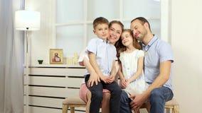 Família que senta-se no sofá e na fala video estoque