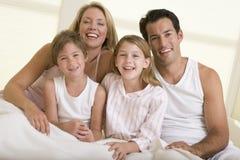 Família que senta-se no sorriso da cama Fotos de Stock Royalty Free