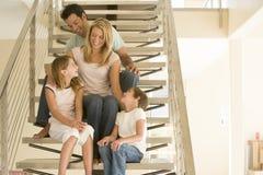 Família que senta-se no sorriso da escadaria Foto de Stock