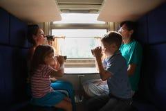 Família que senta-se no trem em assentos azuis imagens de stock