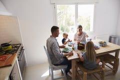 Família que senta-se para baixo para comer o almoço na mesa de cozinha Fotografia de Stock