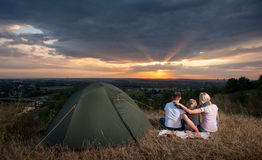 Família que senta-se perto da barraca do acampamento no monte fotografia de stock