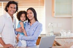 Família que surfa a Web na cozinha junto Imagens de Stock Royalty Free