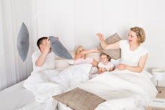 Família que tem a luta de descanso na cama Foto de Stock