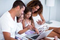 Família que tem o bate-papo video no portátil imagens de stock