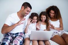 Família que tem o bate-papo video no portátil fotos de stock