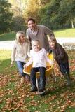 Família que tem o divertimento com as folhas de outono no jardim Fotografia de Stock Royalty Free
