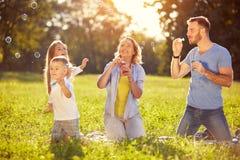 Família que tem o divertimento com bolhas de sabão imagens de stock royalty free
