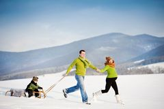 Família que tem o divertimento junto fora no inverno Fotografia de Stock Royalty Free