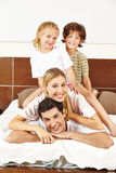 Família que tem o divertimento na cama Fotos de Stock Royalty Free