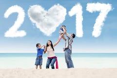 Família que tem o divertimento na costa com 2017 Imagem de Stock