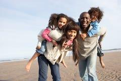 Família que tem o divertimento na praia do inverno imagens de stock