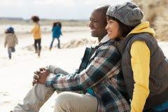 Família que tem o divertimento na praia do inverno fotos de stock