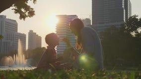 Família que tem o divertimento no parque com lago e arranha-céus no fundo filme