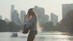 Família que tem o divertimento no parque com lago e arranha-céus no fundo video estoque