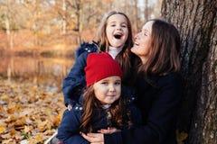 A família que tem o divertimento no parque do outono fora, abraçando, rir, relaxando, aprecia a vida Filhas pequenas de abraço da foto de stock