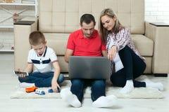 Família que tem o divertimento que chating no Internet com portátil Família que tem imagem de stock royalty free
