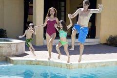 Família que tem o divertimento saltar na piscina foto de stock