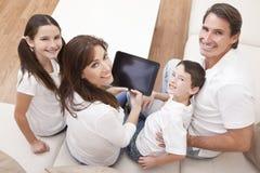Família que tem o divertimento usando o computador da tabuleta em casa Fotos de Stock