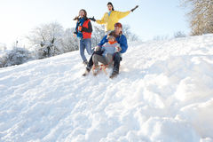 Família que tem o monte nevado de Sledging do divertimento para baixo Fotografia de Stock Royalty Free