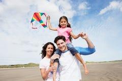 Família que tem o papagaio do voo do divertimento no feriado da praia Fotografia de Stock
