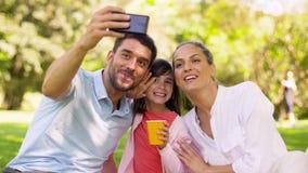 Família que tem o piquenique e que toma o selfie no parque filme
