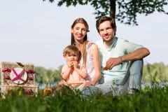 Família que tem o piquenique no lago que senta-se no prado Fotos de Stock Royalty Free