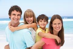 Família que tem o sobreposto na praia imagem de stock