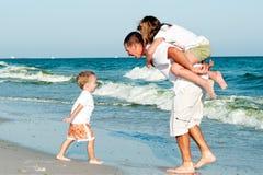 Família que tem o ventilador na praia Fotografia de Stock Royalty Free