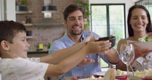 Família que tem a refeição junto na tabela dinning em casa 4k vídeos de arquivo