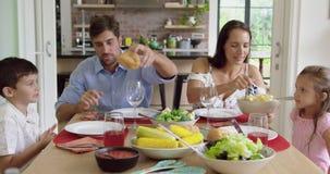 Família que tem a refeição junto na tabela dinning em casa 4k video estoque