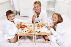 Família que tem um brekfast claro na cama Imagem de Stock Royalty Free