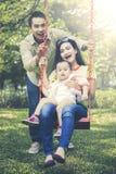 Família que tem uma grande estadia em um parque Fotografia de Stock Royalty Free