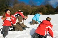 Família que tem uma luta do snowball foto de stock royalty free