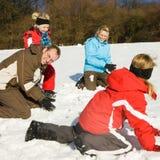 Família que tem uma luta do snowball fotografia de stock