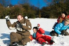 Família que tem uma luta do snowball fotografia de stock royalty free