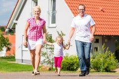 Família que toma a caminhada na frente da casa fotos de stock royalty free