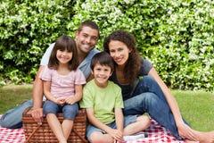Família que toma parte num piquenique no jardim Fotos de Stock Royalty Free