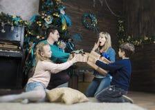 Família que troca presentes na frente do abeto do Natal fotos de stock