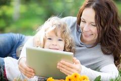 Família que usa o PC da tabuleta fora imagem de stock royalty free