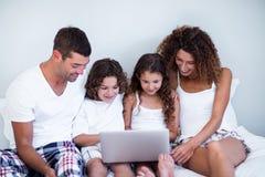 Família que usa o portátil junto na cama imagem de stock royalty free