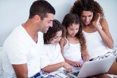 Família que usa o portátil junto na cama foto de stock