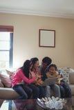 Família que usa o portátil junto na sala de visitas Foto de Stock