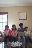 Família que usa o portátil, a tabuleta digital e o telefone celular na sala de visitas Foto de Stock Royalty Free