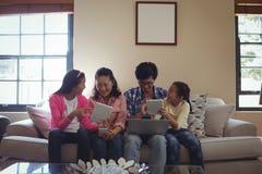 Família que usa o portátil, a tabuleta digital e o telefone celular na sala de visitas Fotos de Stock Royalty Free