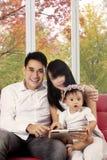 Família que usa a tabuleta digital no sofá Foto de Stock Royalty Free