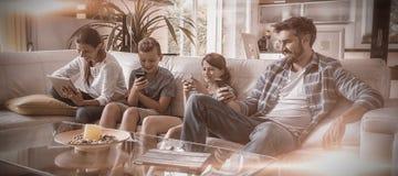 Família que usa a tabuleta e o telefone celular digitais na sala de visitas imagens de stock