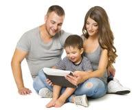 Família que usa a tabuleta, pais felizes com a criança que senta-se sobre o branco fotografia de stock royalty free