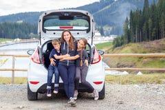 Família que viaja pelo carro e que tem o divertimento no estacionamento Imagens de Stock Royalty Free